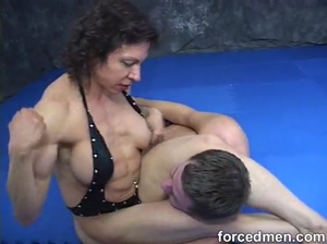 Feeble slave is smothered by scissorhold by body builder mistress