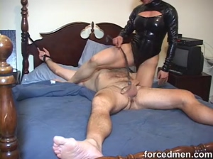 Mistress in latex teases naked man's cock on bed